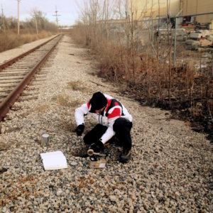 Scientist takes soil samples near railroad track.